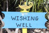image of wishing-well  - The wishing well sign standing next to the well on uninhabited island Little Stirrup Cay  - JPG