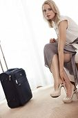 foto of take off clothes  - Full length portrait of young businesswoman taking off her shoes in hotel room - JPG