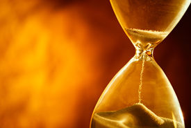 pic of pass-time  - Sand passing through the glass bulbs of an hourglass measuring the passing time as it counts down to a deadline or closure on a yellow background with copyspace - JPG