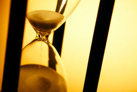 picture of pass-time  - Conceptual image of measuring passing time with a close up view of sand running through an hourglass or egg timer on a golden background with copyspace - JPG
