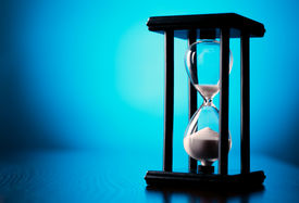 picture of pass-time  - Egg timer or hourglass on a graduated blue background with copyspace in a conceptual image of passing time and time management - JPG