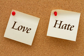 stock photo of hate  - Love versus Hate Two yellow sticky notes on a cork board with the words Love and Hate - JPG