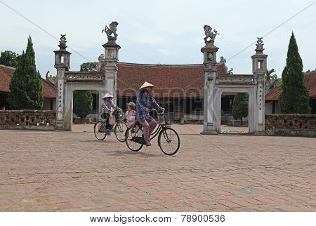 Vietnamese women cycling in front of a temple