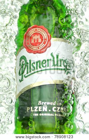Pilsner Urquell pale lager beer in splashed water.