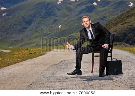 Businessman hitchhiking on a highway