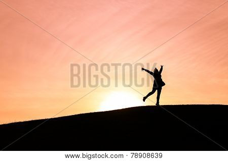 Woman Standing On One Leg With Arms Up In The Air