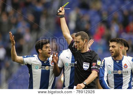 BARCELONA - MARCH, 29: Referee Clos Gomez delivers yellow card to RCD Espanyol players during a Spanish League match against FC Barcelona at the Estadi Cornella on March 29, 2014 in Barcelona, Spain