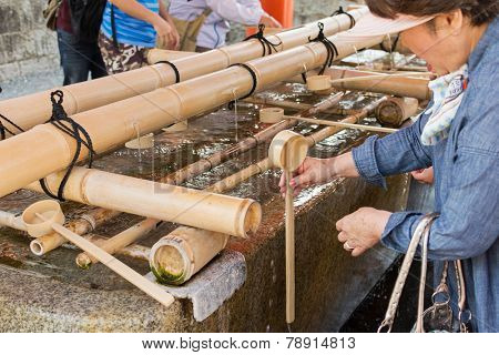 KYOTO, JAPAN - APRIL 27th : visitors wash hands with Japanese water dippers in Fushimi Inari Taisha Shrine in Kyoto, Japan on 27th April 2014.