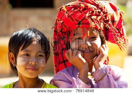 SHAN STATE, MYANMAR - FEBRUARY 3: Unidentified young girls with traditional thanakha on their face on February 3, 2011 in rural area of Shan state, Myanmar. Myanmar women use thanakha for cosmetic purposes.