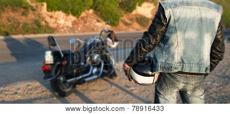 Biker And Motorcycle On The Edge Of The Road