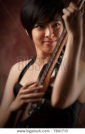 Attractive Multiethnic Girl Plays Her Guitar