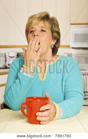 Yawning Woman With Red Coffee Mug In Her Kitchen