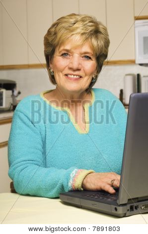 Woman Works On Laptop In Kitchen