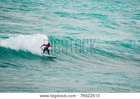 Surfer Riding A Wave In The Blue Sea