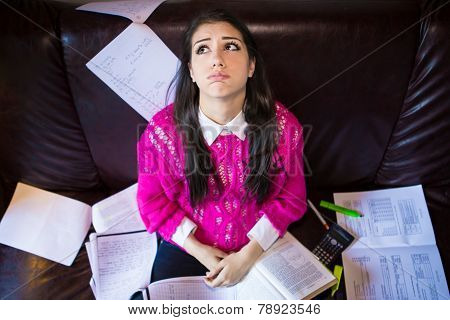 Tired student having a lot to read.Student girl with lot of papers around.Student is studying