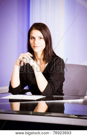 Young beautiful television announcer at studio during live broadcasting.Television anchorwoman