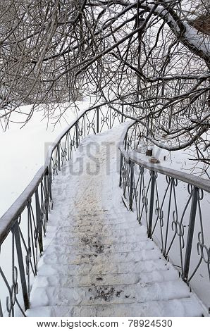 Snow-covered Iron Staircase With Handrails
