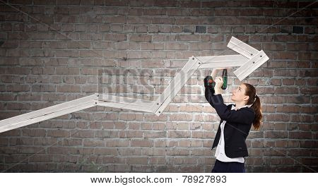 Young businesswoman fixing increasing arrow with drill