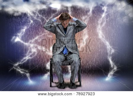 Conceptual image of troubled businessman sitting under rain