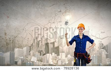 Young woman handyman pointing at electrical bulb