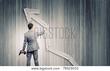 Rear view of businessman fixing wooden graph arrow with drill