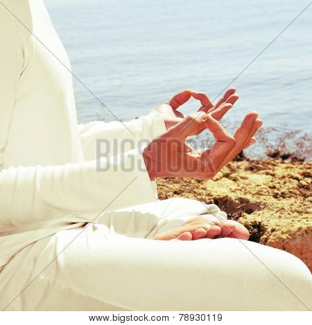 someone meditating in front of the sea, with a retro effect