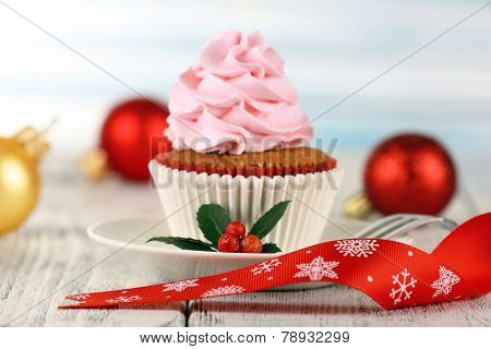 Cup-cake on saucer with Christmas decoration on wooden table and light background