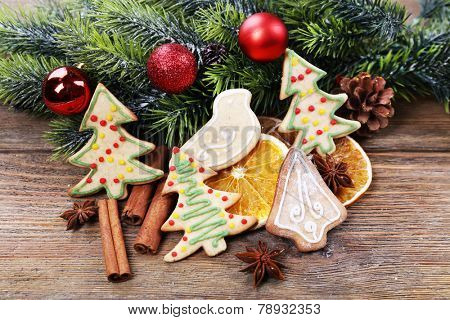 gingerbread cookies with slices of orange and Christmas decoration on wooden table background