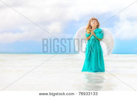 young beautiful angel child girl on natural sea and sky background