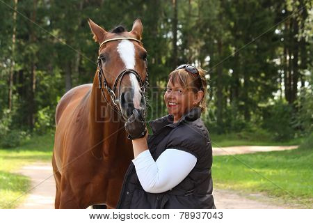 Elderly Happy Woman And Brown Horse In The Forest