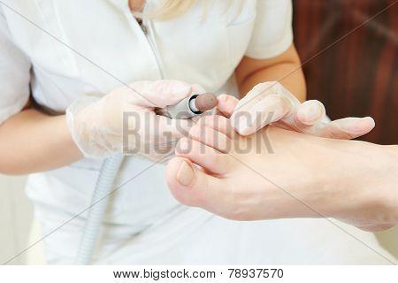 Pedicure technique. Sole treatment during foot care in beauty salon