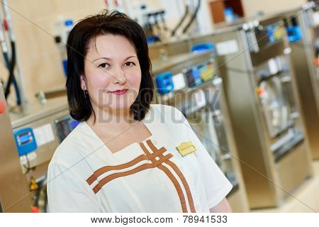 cleaning services. portrait of smiling female laundry worker in front of industrial washing machine