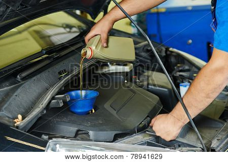 auto mechanic technician replacing and pouring motor oil into automobile engine at maintenance repair service station