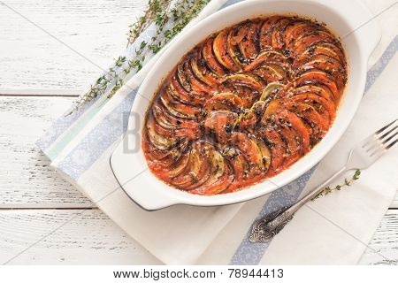 Ratatouille in a baking dish on wooden background