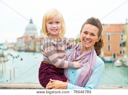 Portrait Of Smiling Mother And Baby Girl Standing On Bridge With