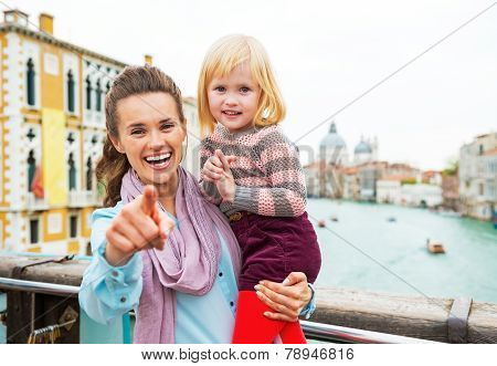 Baby Girl And Mother Poiting In Camera While Standing On Bridge