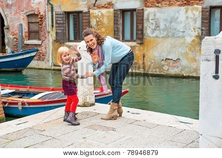 Happy Mother And Baby Girl Waving While Walking In Venice, Italy