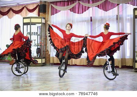 MOSCOW, RUSSIA - MAR 18, 2014: Performance of girls in red dresses on unicycle in hall of Palace of Children and Youth HLW