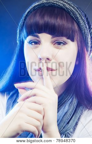Portrait Of Brunette Caucasian Girl In Winter Long Hat Showing Hush! Sign In Studio Environment