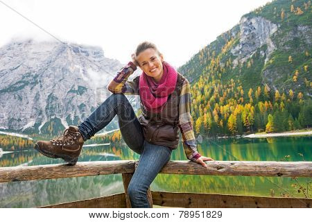 Portrait Of Happy Young Woman Sitting While On Lake Braies In So