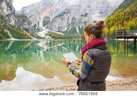 Young Woman Using Tablet Pc While On Lake Braies In South Tyrol,