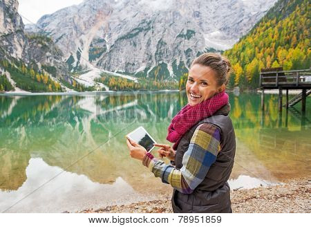 Happy Young Woman With Tablet Pc On Lake Braies In South Tyrol,