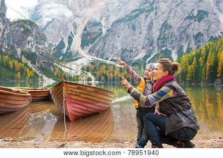 Happy Mother And Baby Pointing On Copy Space While On Lake Braies In South Tyrol, Italy