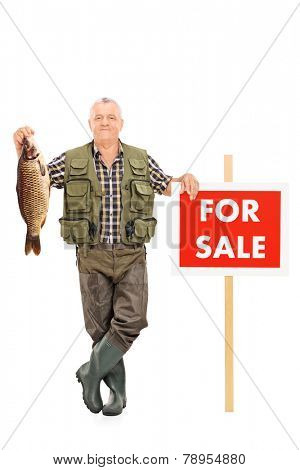 Full length portrait of a smiling mature fisherman holding a fish next to a panel noted �?�¢??For sale�?�¢?�?� isolated on white background