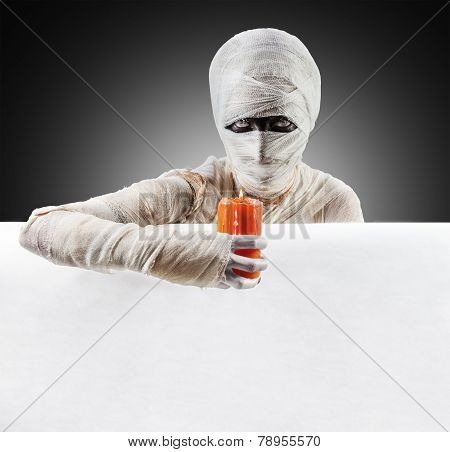 Mummy shining on a poster by candle