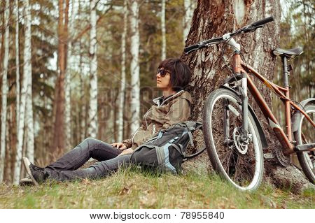 Cyclist woman resting near the tree