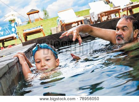 grandfather playing with his grandson in an outdoor pool.