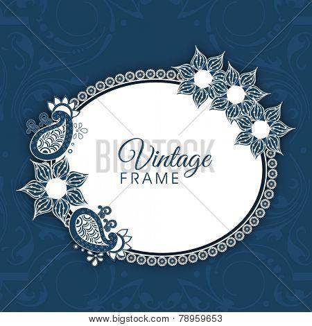 Oval shaped frame with floral design decoration on blue background.