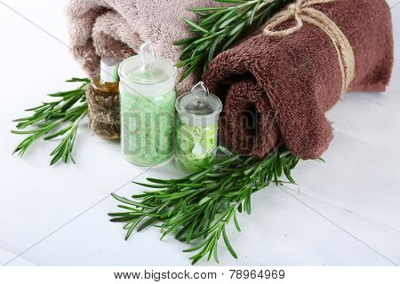 Branches of rosemary, towels and bottle with massage oil and sea salt on color wooden background. Rosemary spa concept