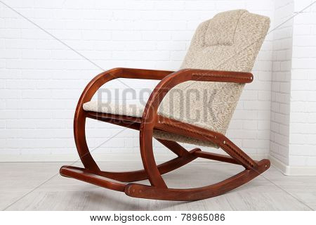 Comfortable rocking-chair on wooden floor near brick wall background